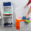 Woman with full laundry basket on home interior background — Stock Photo