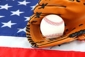 Baseball glove and ball on American flag background — ストック写真