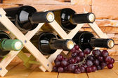 Bottles of wine placed on wooden stand on stone wall background — Stock Photo