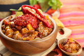 Chili Corn Carne - traditional mexican food, in wooden bowl, on napkin, on wooden background — Stock Photo