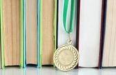 Medalha para a realização em educação com livros close-up — Fotografia Stock