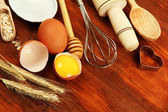 Cooking concept. Basic baking ingredients and kitchen tools on wooden table — Stock Photo