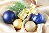 Beautiful Christmas decor on golden satin cloth — Stock Photo