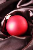 Beautiful Christmas ball on brown satin cloth — Stock Photo