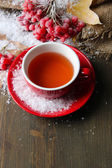 Still life with viburnum tea in cup, berries and snow, on wooden background — Stock Photo