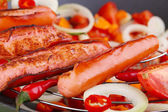 Delicious sausages with vegetables in wok close-up — Stock Photo