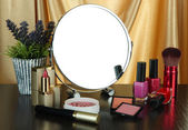 Round table mirror with cosmetics and flowers on table on fabric background — Foto Stock