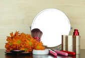 Round table mirror with cosmetics and flowers on table on wooden background — Stock Photo