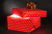 Gift box with bright light on it on dark grey background — Stock Photo