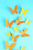 Paper butterflies on blue wooden board background — Stock Photo