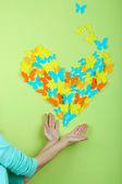 бумажные бабочки на руках на фоне зеленая стена — Стоковое фото