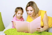 Little girl with mom read book in bed — Стоковое фото