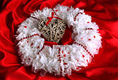 Decorative wreath with wicker heart on fabric background — Stock Photo
