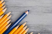 Celebratory pencil among usual pencils, on color background — Stockfoto