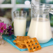 Pitcher and glass of milk with cookies on wooden table on window background — Stock Photo
