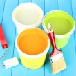 Set for painting: paint pots, brushes, paint-roller on blue wooden table — Stock Photo #35572857