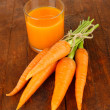 Heap of carrots, glass of juice, on wooden background — Stockfoto