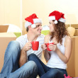 Young couple with boxes in new home celebrating New Years — Stockfoto