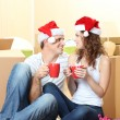 Young couple with boxes in new home celebrating New Years — Stock Photo #35574509