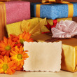 Gift boxes with blank label and flowers on table on brown background — Stok fotoğraf