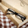 Composition with old book, eye glasses and plaid on wooden background — Stock Photo #35575123