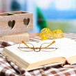 Stock Photo: Composition with old book, eye glasses, candles, and plaid on bright background