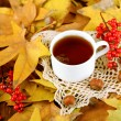 Stock Photo: Cup of hot beverage, on yellow leaves background