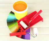 Set for painting: paint pot, paint-roller on white wooden table — Stock Photo