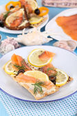 Salmon sandwiches on plate on wooden table close-up — Stock Photo