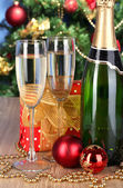Bottle of champagne with glasses and Christmas balls on wooden table on Christmas tree background — 图库照片