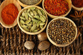 Many different spices and fragrant herbs on braided table close-up — Foto Stock