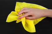 Hand wiping wooden surface with yellow rag — Stock Photo