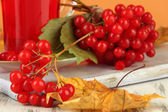 Red berries of viburnum and cup of tea on table close up — Photo