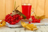 Red berries of viburnum and cup of tea on table on wooden background — Photo