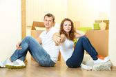 Young couple with keys to your new home on room background — 图库照片