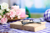 Composition with old book, eye glasses, candles, flowers and plaid on bright background — Stock Photo