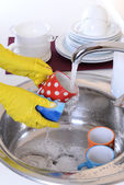 Close up hands of woman washing dishes in kitchen — Stock Photo