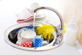 Stack of dishes soaking in kitchen sink — Stock Photo