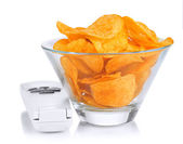Chips in bowl and TV remote isolated on white — Foto Stock