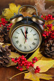 Old clock on autumn leaves on wooden table close-up — Stock fotografie