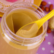 Delicious peanut butter in open bank on purple background with polka dots close-up — Stock Photo