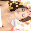 Beautiful young woman during facial massage in cosmetic salon close up — Stock Photo
