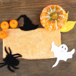 Old paper with Halloween decorations on grey wooden background — Stock Photo