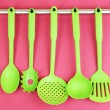 Plastic kitchen utensils on silver hooks on red background — Stock Photo #35694753