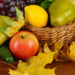 Different fruits and vegetables with yellow leaves in basket on table on bright background — Stock Photo #35694869