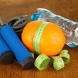 Orange with measuring tape,skipping rope and bottle of water, on wooden background — Stock Photo