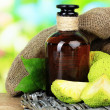 Osage Orange fruits (Maclurpomifera) and medicine bottle, on wooden table, on nature background — Stock Photo #35695991