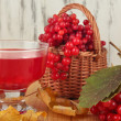 Red berries of viburnum in basket with jam on table on wooden background — Stock Photo