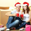 Young couple with boxes in new home celebrating New Years — Stock Photo