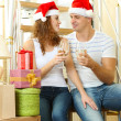 Young couple celebrating New Years in new home on stairs background — Stock Photo